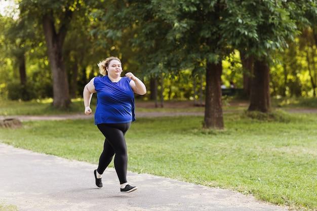 Młoda blondynka dużych rozmiarów biegnie w parku pojęcie zdrowego stylu życia