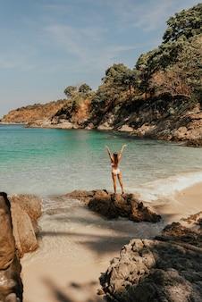 Młoda blondynka europejka w białym stroju kąpielowym bikini na plaży