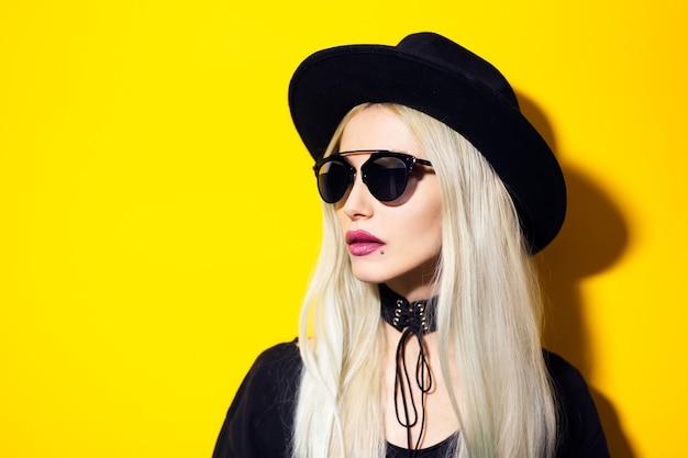 Młoda blondynka hipster dziewczyna z różowymi ustami, na sobie okulary przeciwsłoneczne, czarny kapelusz i naszyjnik, na białym tle na żółtej ścianie.