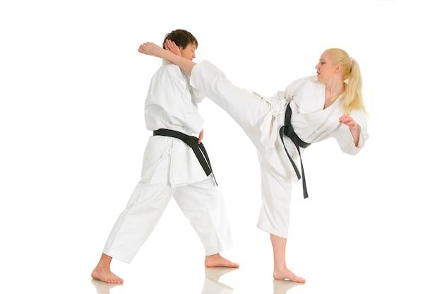 Młoda blondynka i młody bezczelny facet karateka trenują w kimono. koncepcja przygotowania do mistrzostw.