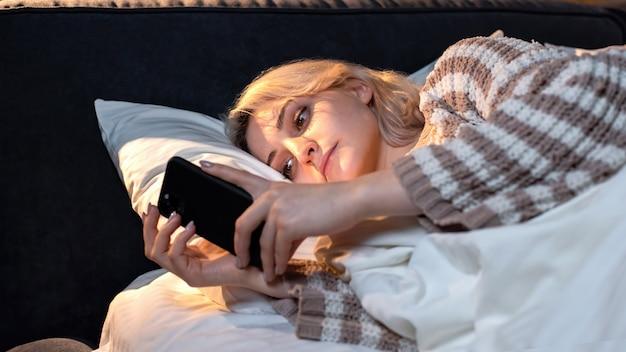 Młoda blondynka jest na swoim smartfonie w łóżku. próbuję zasnąć. uzależnienie od mediów społecznościowych