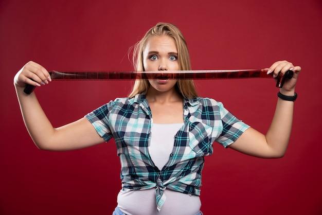 Młoda blondynka jest zdezorientowana i zawiedziona podczas oglądania polaroidu.