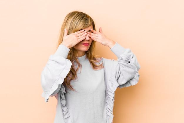 Młoda blondynka kaukaska boi się zakrywających oczy rękami.