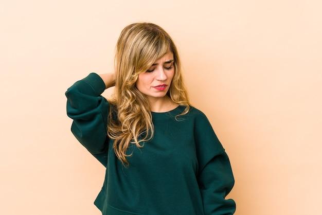 Młoda blondynka kaukaska cierpi na ból szyi z powodu siedzącego trybu życia.