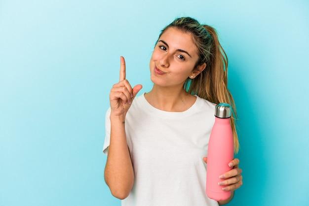 Młoda blondynka kaukaska kobieta trzyma termo na białym tle na niebieskim tle pokazuje numer jeden z palcem.
