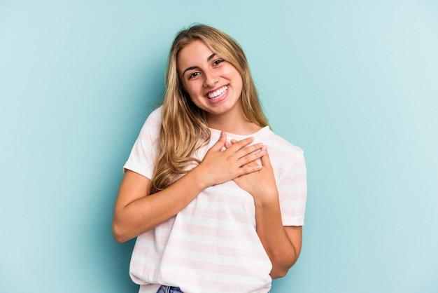 Młoda blondynka kaukaska na białym tle na niebieskim tle ma przyjazny wyraz, przyciskając dłoń do klatki piersiowej. koncepcja miłości.