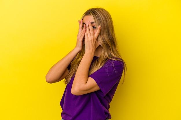 Młoda blondynka kaukaska na białym tle na żółtym tle mruga przez palce przestraszona i zdenerwowana.