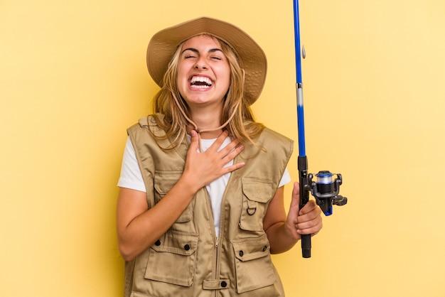 Młoda blondynka kaukaska rybaczka trzymająca wędkę na żółtym tle śmieje się głośno trzymając rękę na klatce piersiowej.