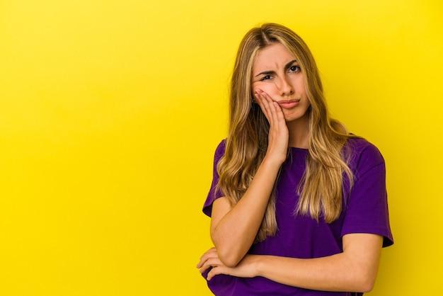 Młoda blondynka kaukaski kobieta na białym tle na żółtej ścianie, która czuje się smutna i zamyślona, patrząc na miejsce.