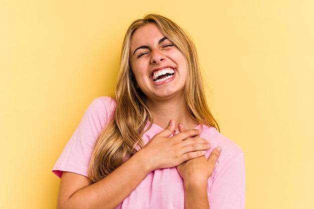 Młoda blondynka kaukaski kobieta na białym tle na żółtym tle śmiejąc się trzymając ręce na sercu, pojęcie szczęścia.