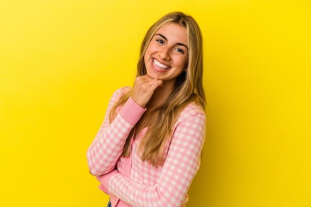 Młoda blondynka kaukaski kobieta na białym tle na żółtym tle uśmiechnięta szczęśliwa i pewna siebie, dotykając podbródka ręką.