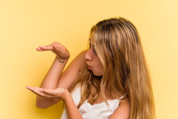 Młoda blondynka kaukaski kobieta na białym tle na żółtym tle w szoku i zdziwieniu, trzymając kopię przestrzeni między rękami.