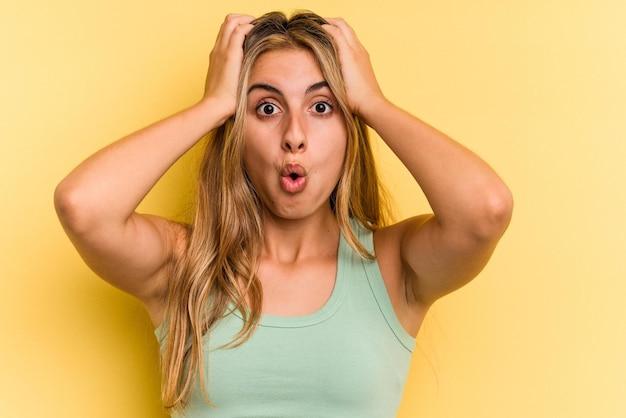 Młoda blondynka kaukaski kobieta na białym tle na żółtym tle zaskoczony i zszokowany.