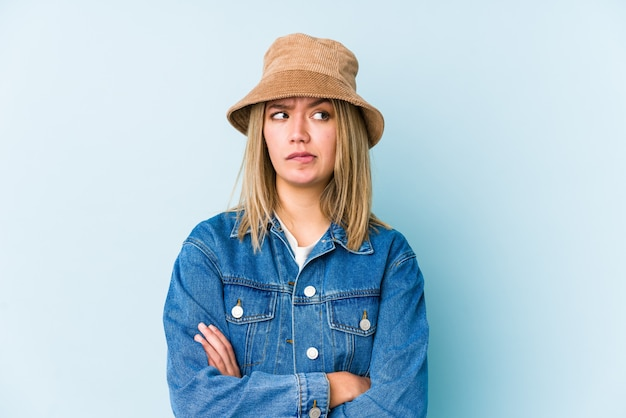 Młoda blondynka kaukaski kobieta na białym tle niezadowolony patrząc w kamerę z sarkastycznym wyrazem.