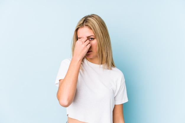 Młoda blondynka kaukaski kobieta na białym tle o ból głowy, dotykając przodu twarzy.