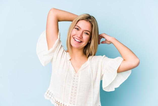 Młoda blondynka kaukaski kobieta na białym tle rozciąganie ramion, zrelaksowana pozycja.