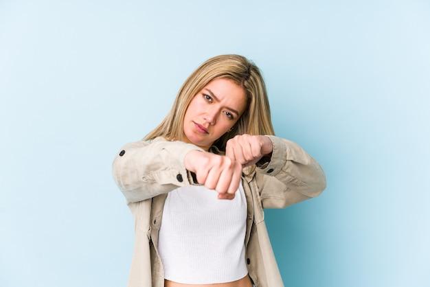 Młoda blondynka kaukaski kobieta na białym tle rzuca cios, złość, walka z powodu kłótni, boks.