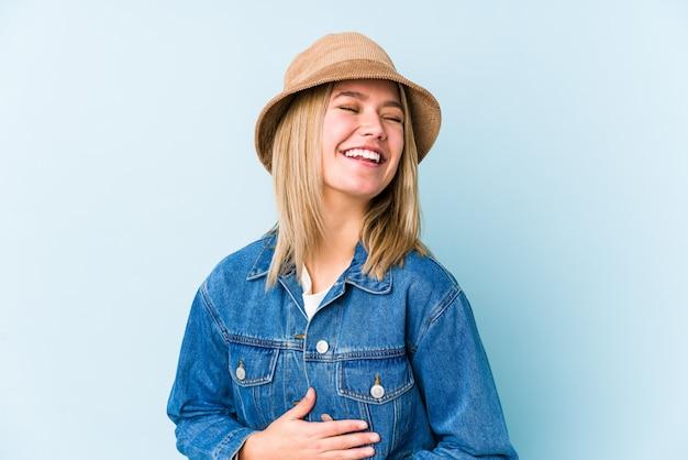 Młoda blondynka kaukaski kobieta na białym tle śmieje się szczęśliwie i dobrze się trzyma na rękach na brzuchu.