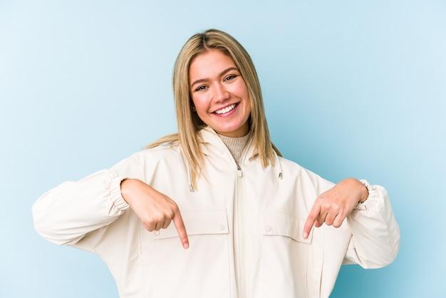 Młoda blondynka kaukaski kobieta na białym tle stojąca z wyciągniętą ręką pokazując znak stopu, uniemożliwiając ci.