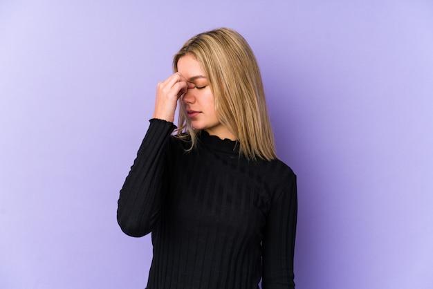 Młoda blondynka kaukaski kobieta o ból głowy, dotykając przodu twarzy.