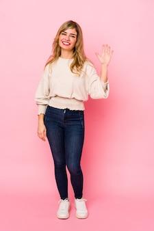 Młoda blondynka kaukaski kobieta stojąca na różowo uśmiechnięty wesoły pokazując numer pięć palcami.