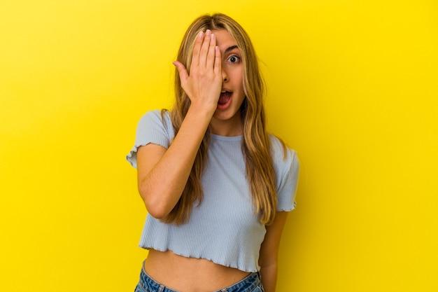 Młoda blondynka kaukaski zabawy obejmujące połowę twarzy dłonią.