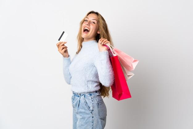 Młoda blondynka kobieta na białym tle gospodarstwa torby na zakupy i karty kredytowej
