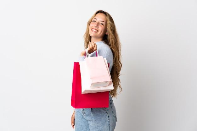 Młoda blondynka kobieta na białym tle gospodarstwa torby na zakupy i uśmiechnięte