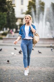 Młoda blondynka kobieta rozmawia przez telefon na placu ulicznym, ubrana w dżinsowy apartament z torbą na ramieniu w słoneczny dzień