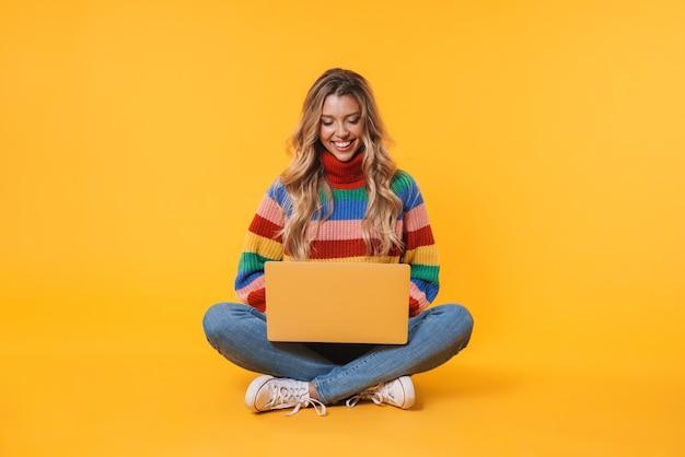 Młoda blondynka korzystająca z laptopa siedząc na podłodze odizolowanej nad żółtą ścianą