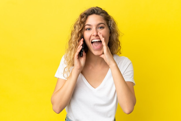 Młoda blondynka korzystająca z telefonu komórkowego odizolowanego na żółtym tle krzyczy z szeroko otwartymi ustami