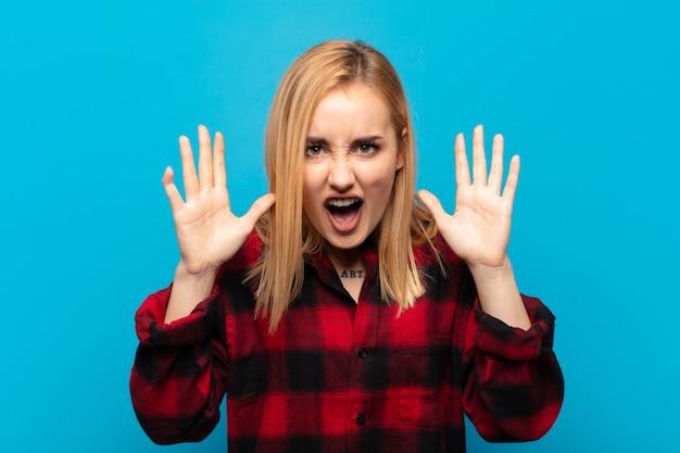 Młoda blondynka krzyczy w panice lub złości, zszokowana, przerażona lub wściekła, z rękami przy głowie