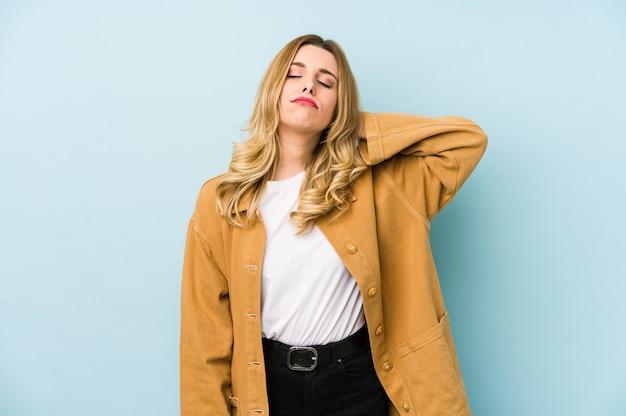 Młoda blondynka ładna kobieta na białym tle cierpi na ból szyi z powodu siedzącego trybu życia.