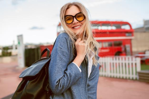 Młoda blondynka, ładna kobieta spacerująca po centrum londynu, ubrana w stylowy, elegancki strój studencki, niebieski płaszcz i kolorowe okulary, okres jesienno-wiosenny w środku sezonu, podróżniczy nastrój.