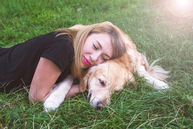 Młoda blondynka leży na trawie ze swoim psem. pies rasy retriever z dziewczyną w parku.
