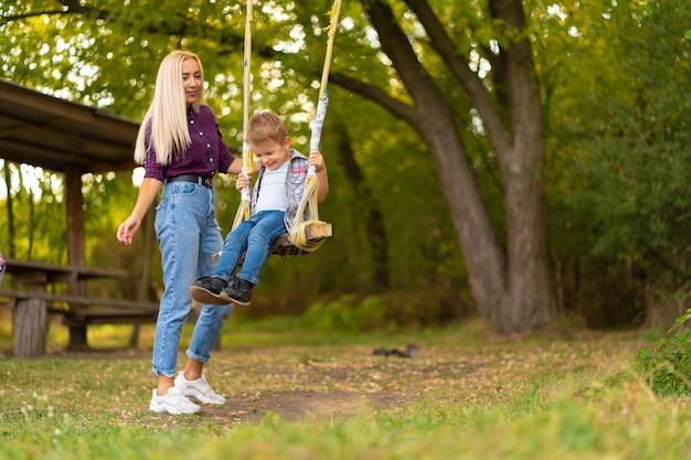 Młoda blondynka mama potrząsa swoim małym synkiem na huśtawce w zielonym parku. szczęśliwe dzieciństwo.