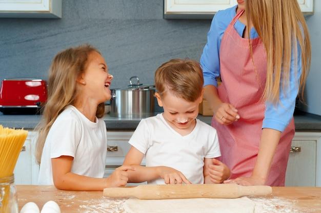 Młoda blondynka, matka i jej dzieci bawią się podczas gotowania ciasta