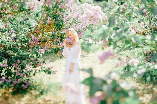 Młoda blondynka modela kobieta w biel sukni pozuje w pogodnym parku.