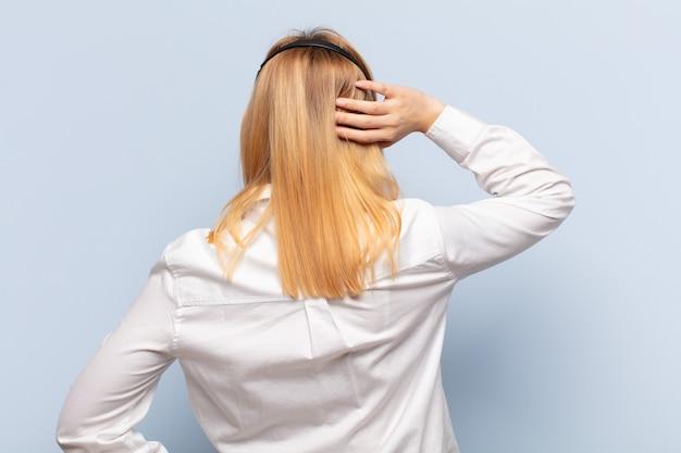 Młoda blondynka myśli lub wątpi, drapie się po głowie, czuje się zdziwiona i zdezorientowana, widok z tyłu lub z tyłu