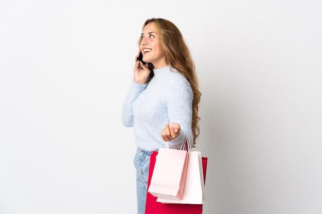 Młoda blondynka na białym tle gospodarstwa torby na zakupy i dzwoniąc do znajomego ze swoim telefonem komórkowym