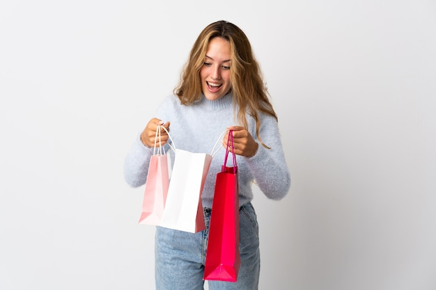 Młoda blondynka na białym tle gospodarstwa torby na zakupy i patrząc wewnątrz niego