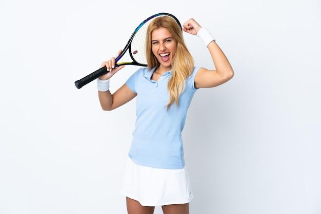 Młoda blondynka na białym tle gra w tenisa i świętuje zwycięstwo