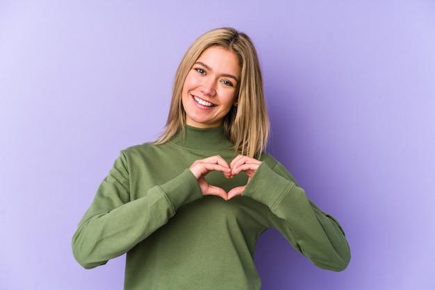 Młoda blondynka na białym tle uśmiechając się i pokazując kształt serca rękami