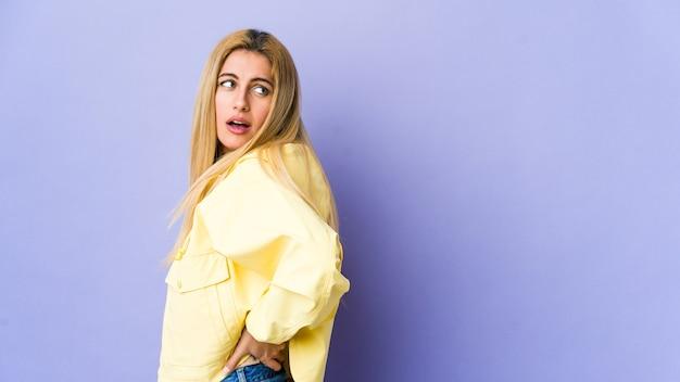 Młoda blondynka na fioletowej ścianie cierpi na ból pleców.