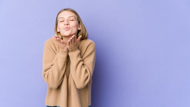 Młoda blondynka na fioletowej ścianie składane usta i trzymając dłonie, aby wysłać pocałunek