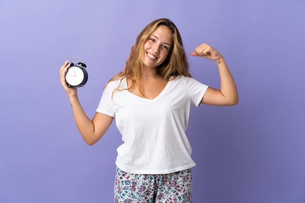 Młoda blondynka na fioletowej ścianie w piżamie i trzymając zegar podczas robienia silnego gestu