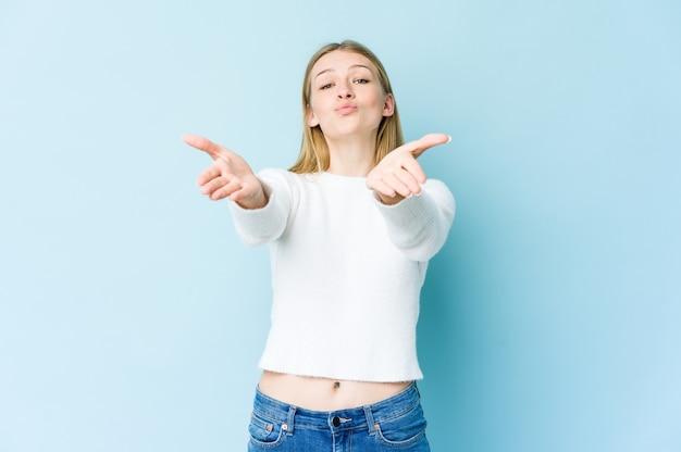 Młoda blondynka na niebieskiej ścianie składane usta i trzymając dłonie, aby wysłać pocałunek.