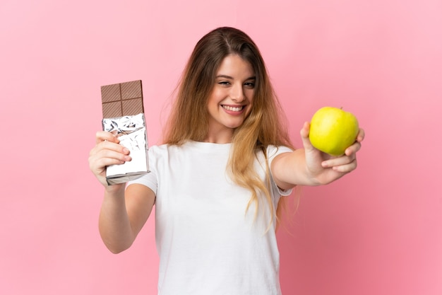 Młoda blondynka na odizolowanej ścianie biorąc tabletkę czekolady w jednej ręce i jabłko w drugiej