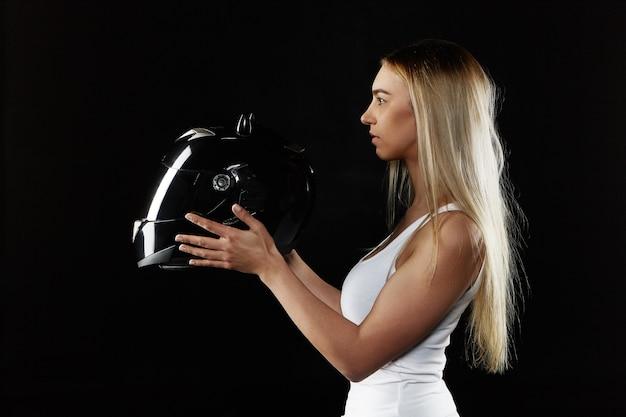Młoda blondynka na sobie biały podkoszulek, trzymając czarny kask. atrakcyjna dziewczyna sportowy pozowanie na białym tle ze sprzętem ochronnym. sporty ekstremalne i transport