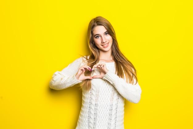 Młoda blondynka na żółtym tle zakochuje się pokazuje znak serca w dłoniach